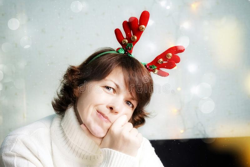Pretty young Santa girl in knitted sweater, fun decorative deer horns on head pointing hand aside on red royalty free stock photography