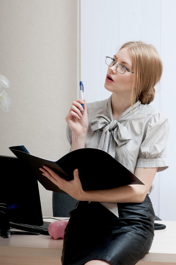 Pretty young secretary. Pretty young secretary thinks about the report stock photo