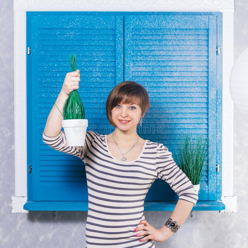 Pretty young short haired caucasian girl holding potted plant near blue window. Studio shot, gardening concept, copy space. stock image