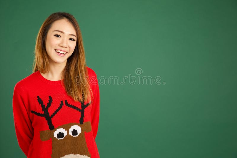 Pretty young singaporean girl wearing Christmas jumper and smiling. Over green background royalty free stock images