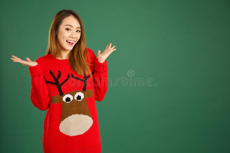Pretty young singaporean girl wearing Christmas jumper and smiling. Over green background royalty free stock photography