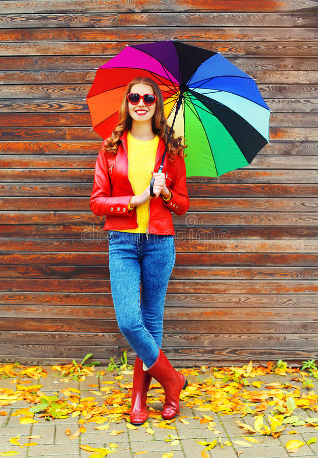 Pretty young smiling woman with colorful umbrella wearing a red leather jacket and rubber boots in autumn over wooden background. Yellow leafs royalty free stock photos