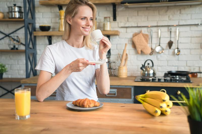 Pretty young smiling woman is sitting in the kitchen at home, having breakfast, drinking coffee with croissants and looking stock photography