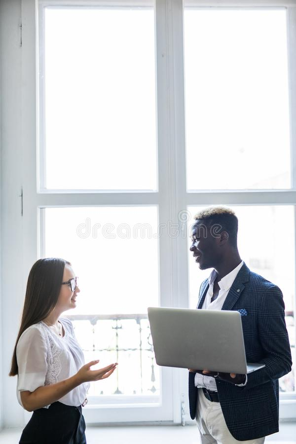 This is it. Pretty young asian business woman pointing at laptop while standing near her happy afro business man in front of stock photos