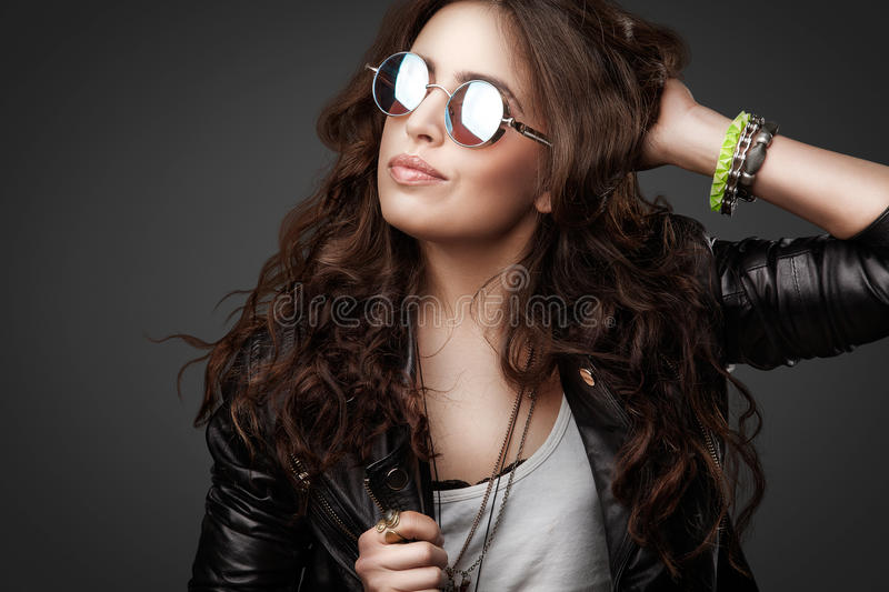 Pretty young stylish girl in leather jacket and round sunglasses royalty free stock photography