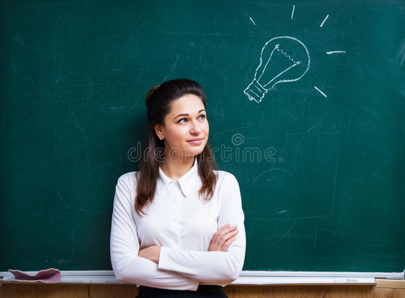 Young teacher comes up with an idea near the board stock photo