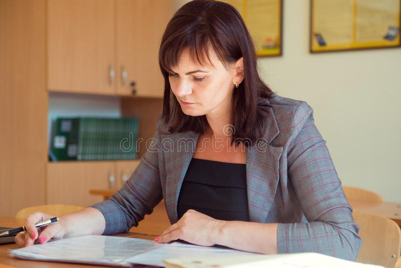 Pretty young teacher is sitting with books in classroom royalty free stock photos