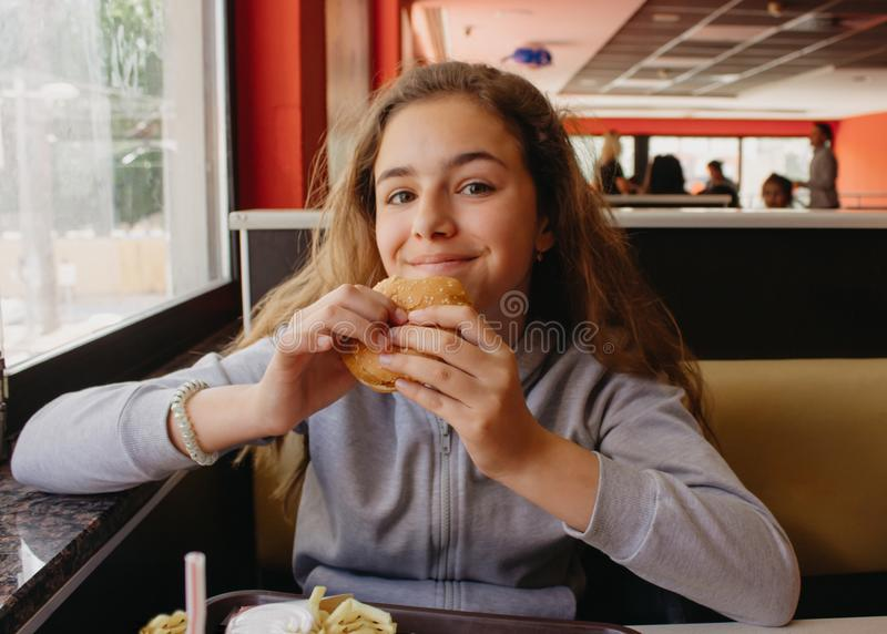 Pretty young teen girl with an appetite eating a hamburger in a cafe royalty free stock photography