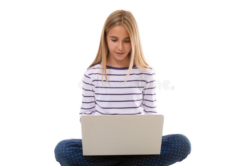 Pretty young teen girl sitting on the floor with crossed legs and using laptop, isolated stock photography