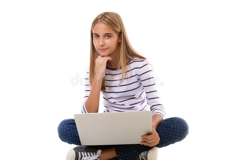 Pretty young teen girl sitting on the floor with crossed legs and using laptop,isolated stock image