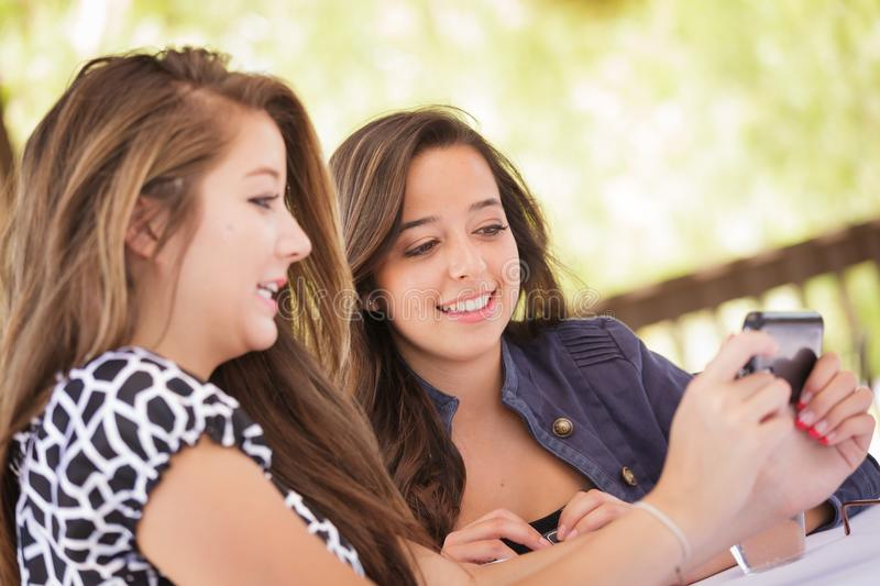 Pretty Young Teen Girlfriends Using Their Smart Phone. Expressive Young Adult Girlfriends Using Their Smart Cell Phone Outdoors stock image