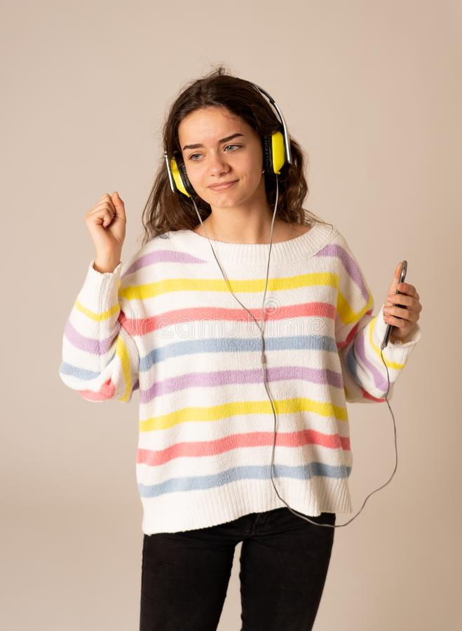 Pretty young teenager girl in headphones listening to music and dancing isolated on grey background royalty free stock image