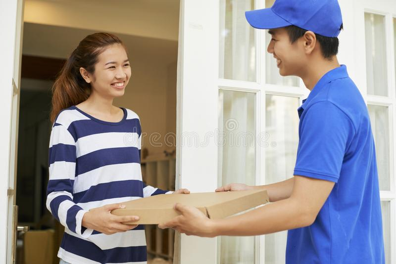Cheerful woman receiving hot pizza. Pretty young Vietnamese women happy to receive hot pizza she ordered via delivering platform stock images