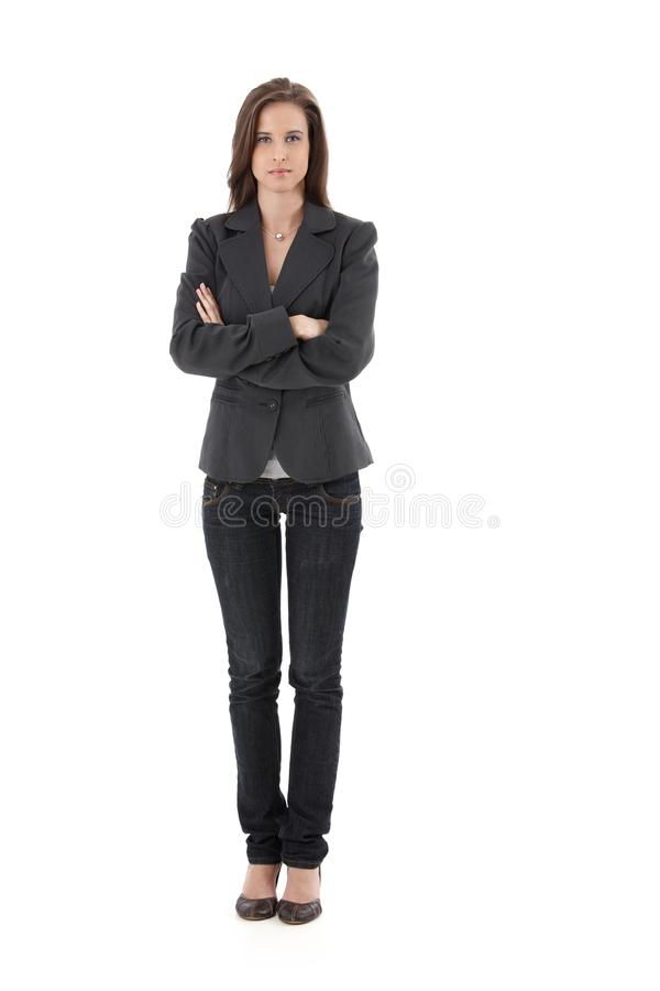 Pretty young woman with arms folded. Pretty young businesswoman standing with arms folded, looking at camera, isolated on white, full length royalty free stock images