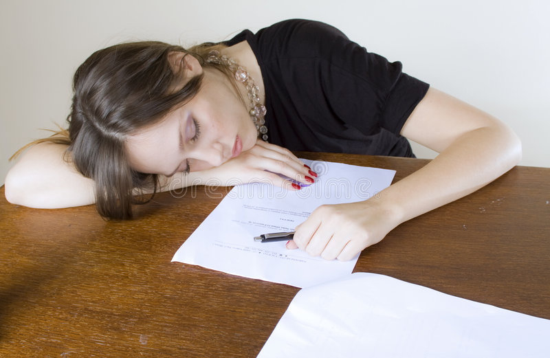 Pretty young woman asleep at the office table royalty free stock image