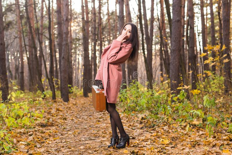 Pretty young woman in autumn park posing with suitcase royalty free stock photos