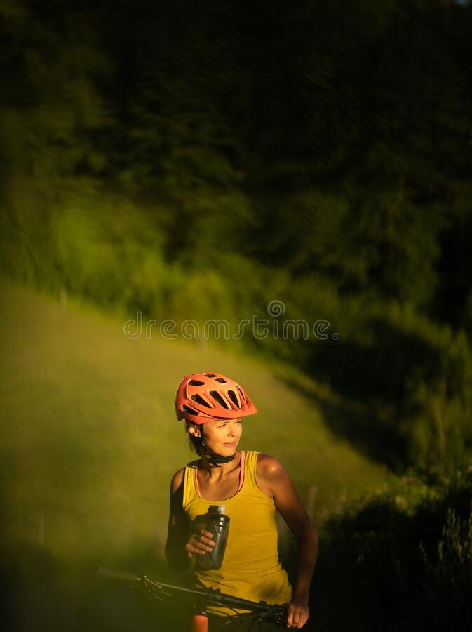 Pretty, young woman biking on a mountain bike royalty free stock image