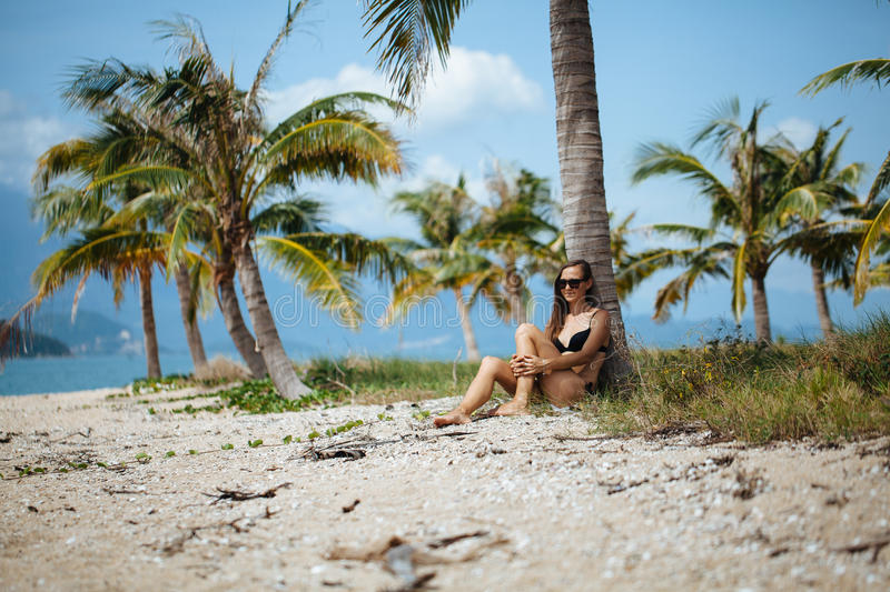 Pretty young woman in bikini is relax on a tropical beach under palm tree royalty free stock photo