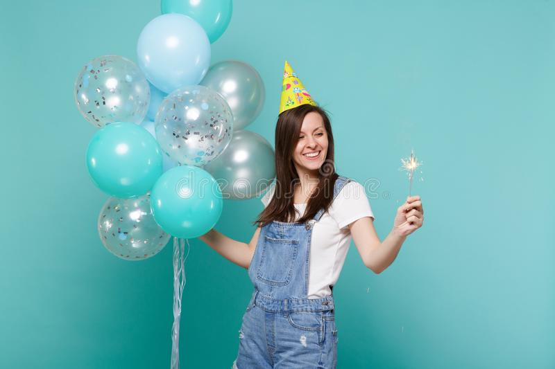 Pretty young woman in birthday hat looking on burning sparkler in hand celebrating holding colorful air balloons. Isolated on blue turquoise background royalty free stock photos