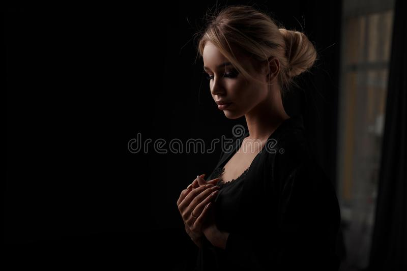 Pretty young woman in black clothes at night in a dark room. royalty free stock photography