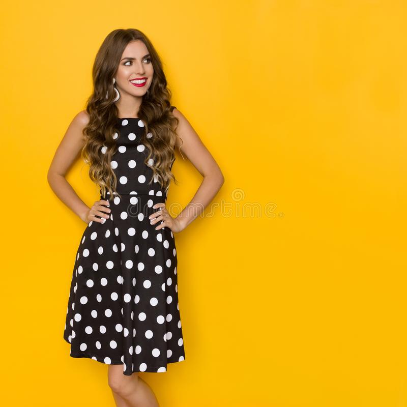 Pretty Young Woman In Black Coctail Dress In Polka Dots Is Looking Away And Smiling royalty free stock photo
