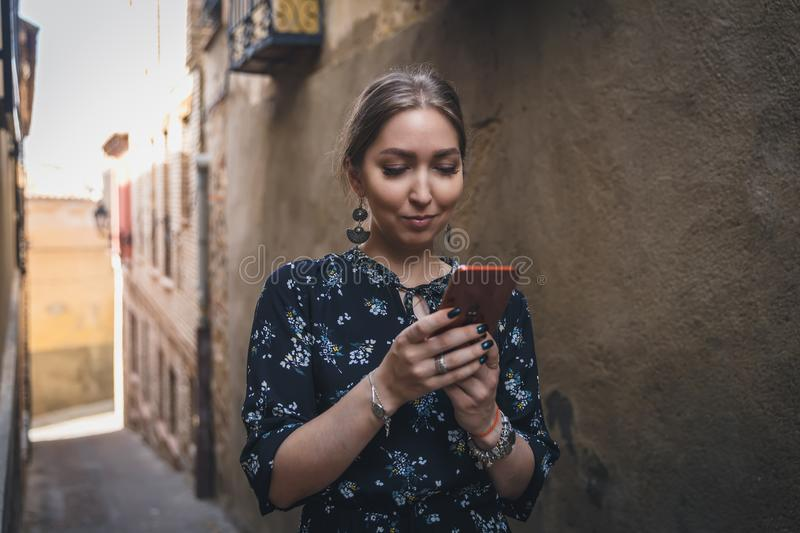 Pretty young woman in a black dress using smartphone at old town street. Travel by Europe. Toledo, Spain. Pretty young woman in a black dress using smartphone royalty free stock photos