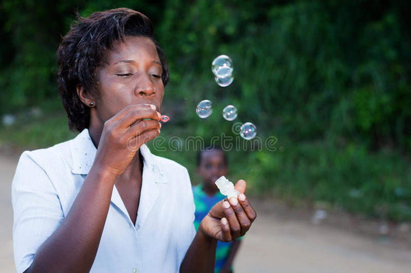 Pretty young woman blowing bubbles. Pretty young woman blowing bubbles and her child looks in the background stock photo