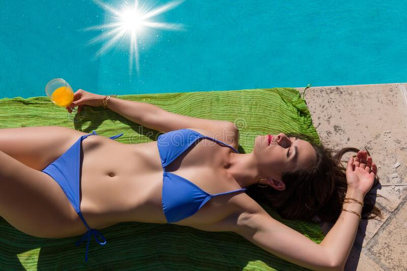 Closeup of a woman at swimming pool lying down royalty free stock photos
