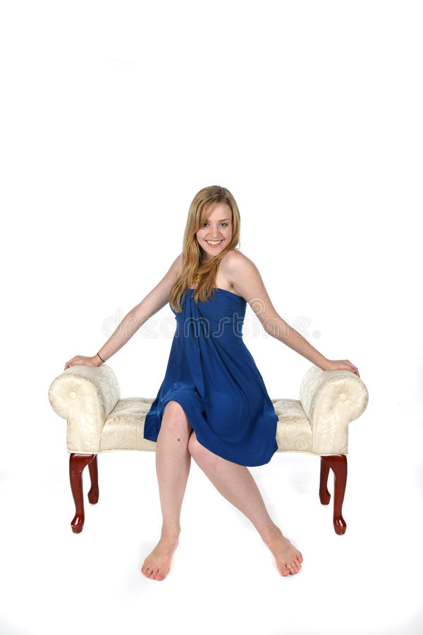 Pretty young woman in blue dress sitting on bench stock image