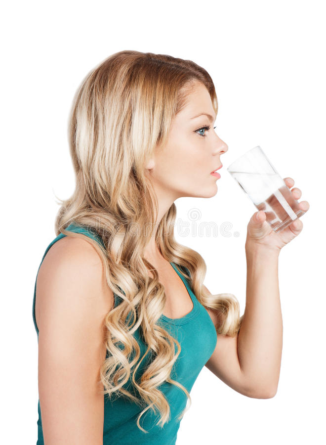 Pretty young woman in blue singlet is holding a gl. Beautiful blonde long-haired girl is drinking water from glass on white. Studio shot stock photo