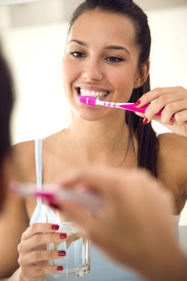 Pretty young woman brushing her teeth in the bathroom. stock photo