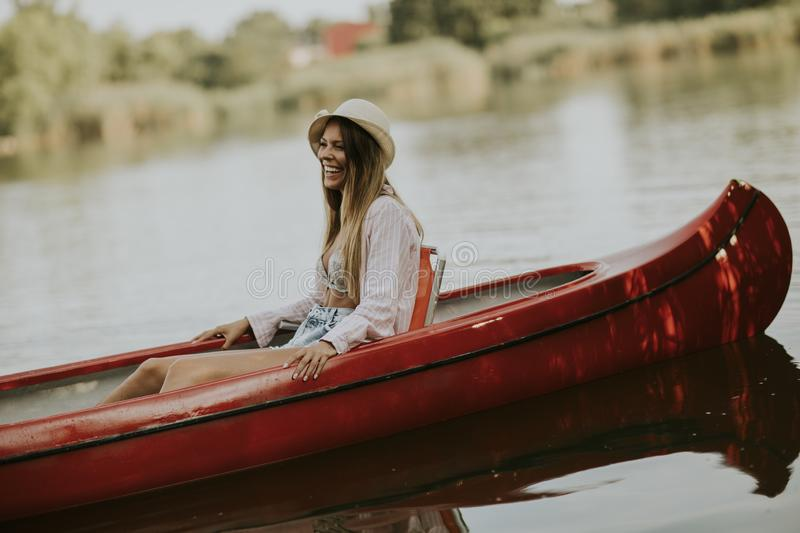 Pretty young woman in the canoe on the lake. At summer day royalty free stock images