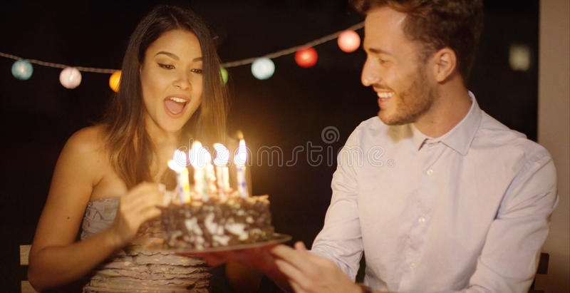 Pretty young woman celebrating her birthday. Pretty young women celebrating her birthday blowing out the candles on the cake at a party watched by her loving royalty free stock image