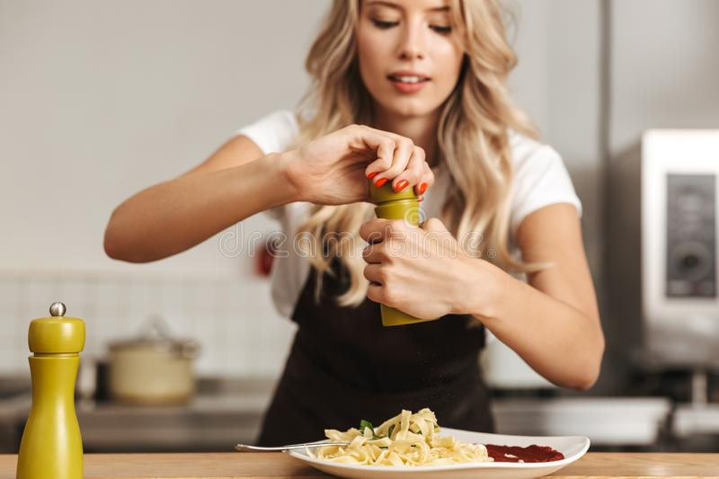 Pretty young woman chef putting salt stock images