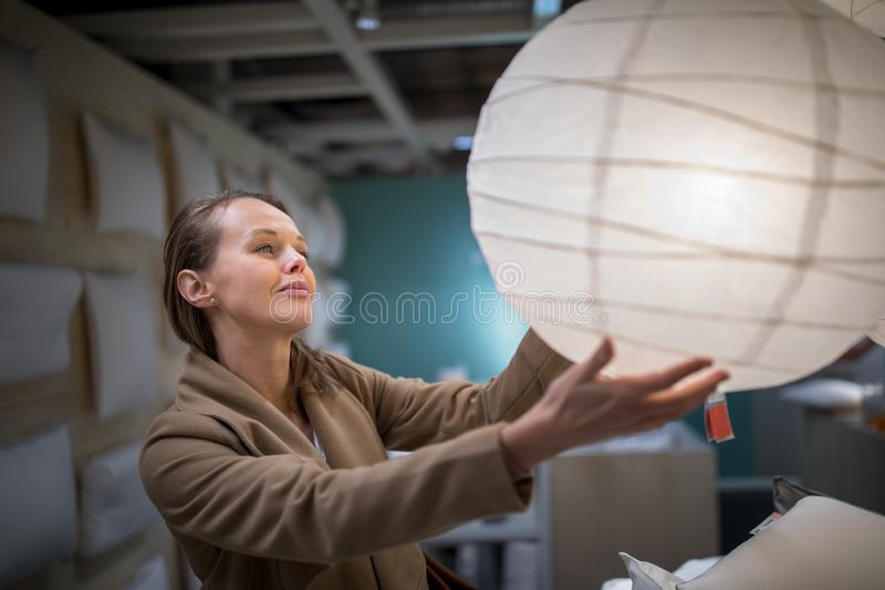 Pretty, young woman choosing the right lamp for her apartment royalty free stock photography