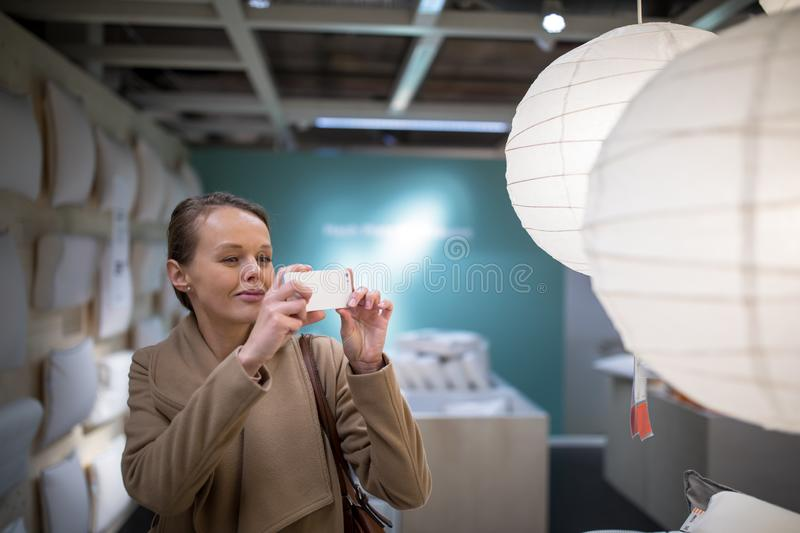 Pretty, young woman choosing the right lamp for her apartment royalty free stock images