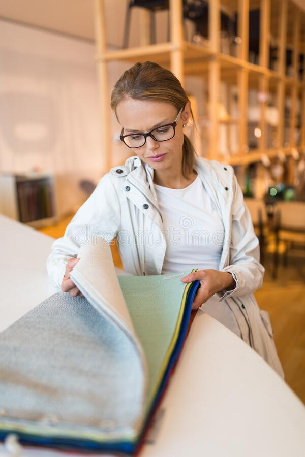 Pretty young woman  choosing the right material/color for her modern appartement interior royalty free stock photography