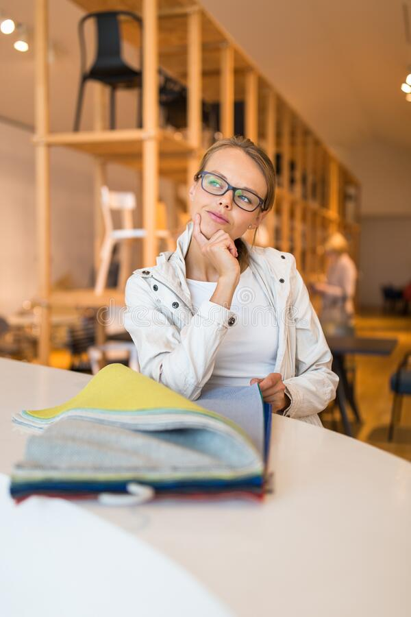 Pretty young woman  choosing the right material/color for her modern appartement interior stock photos