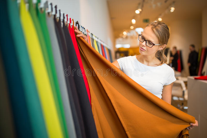 Pretty young woman choosing the right material/color. For her modern appartement interior shallow DOF; color toned image royalty free stock photo