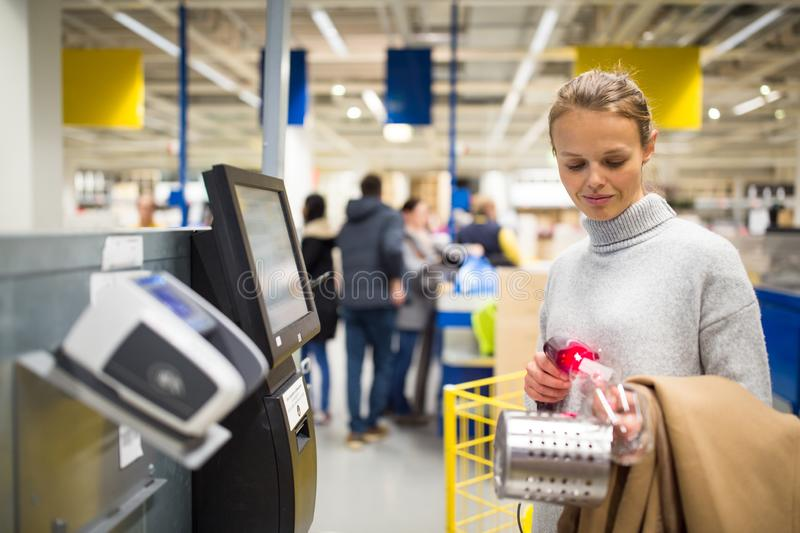 Pretty, young woman choosing the right stuff for her apartment in a modern home furnishings store royalty free stock photos