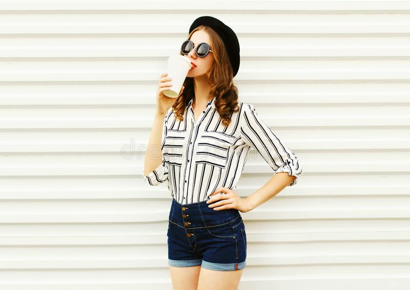 Pretty young woman with coffee cup in black round hat, shorts, white striped shirt on white wall. Background stock image