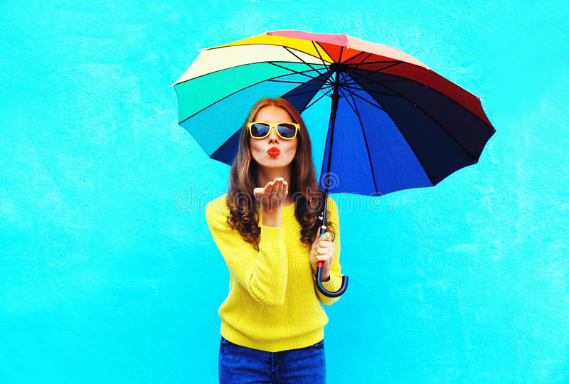 Pretty young woman with colorful umbrella sends air sweet kiss in autumn day over blue background wearing yellow knitted sweater. Pretty young woman with royalty free stock photo