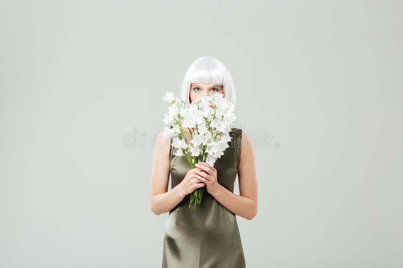 Pretty young woman covered her face with bouquet of flowers stock photos
