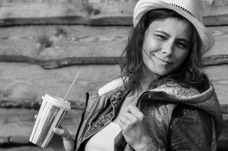 Pretty young woman in cowboy hat. Black and white portrait of attractive girl in jeans jacket on wooden fence background. stock photos