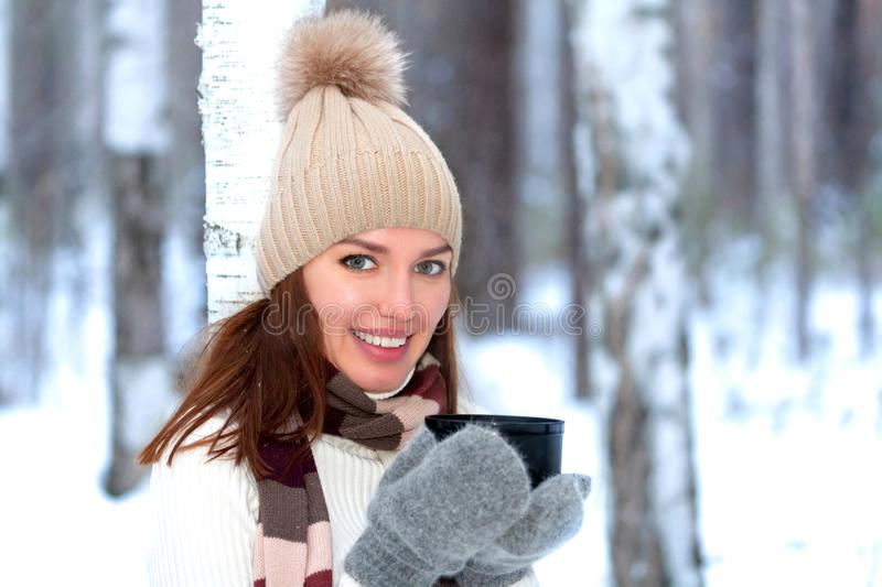 Pretty young woman with a cup of hot tea or coffee is posing in a winter forest or park stock image