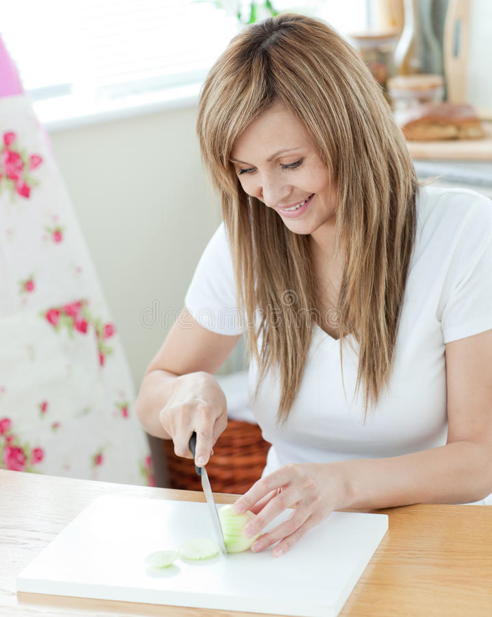 Pretty Young Woman Cutting Onions In The Kitchen Royalty Free Stock Photos