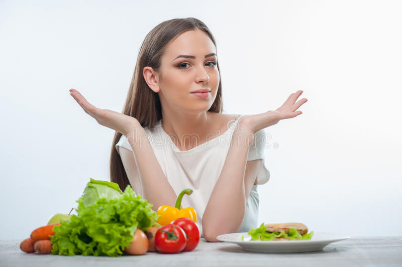 Pretty young woman does not know what to eat. Beautiful girl can not choose between healthy and unhealthy food. She gesturing and looking at the camera confused stock images