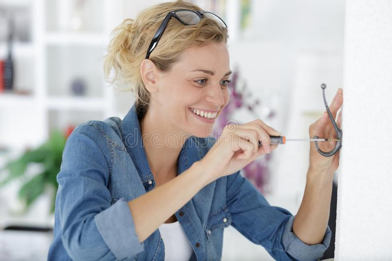 Pretty young woman doing diy work at home stock photo