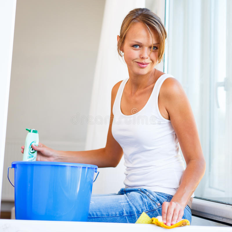 Pretty, young woman doing house work - washing windows. (shallow DOF; color toned image royalty free stock photos