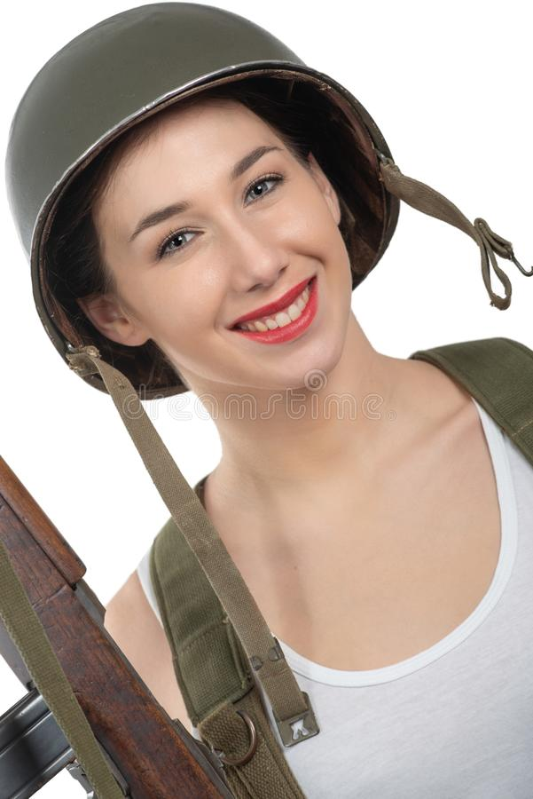 Pretty young woman dressed in wwii military uniform with helmet and rifle royalty free stock photos